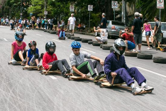 Crianças, usando capacetes, descem a rua em carrinhos de rolimã