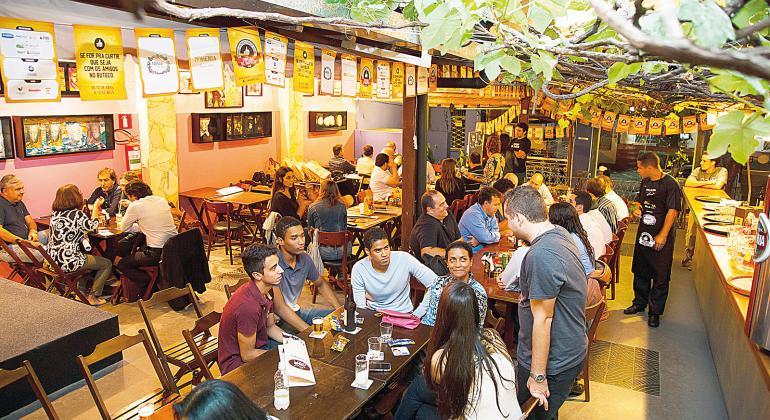 Cerca de 30 jovens e adultos bebem cerveja e conversam em mesas de bar à tarde. Foto: Divulgação