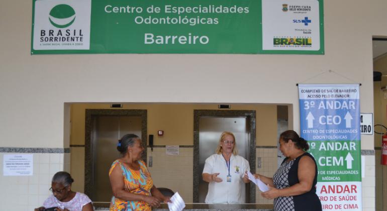 Atendente do Centro de Especialidades Odontológicas Barreiro Atende a duas  mulheres de pé, à esquerda d90fd83b96