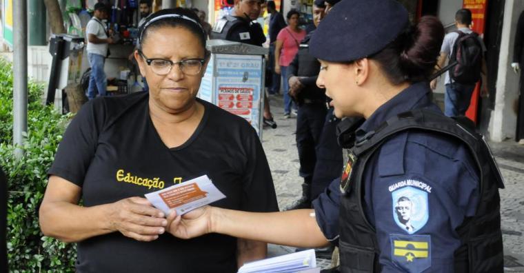 mulher recebe instruções de guarda municipal