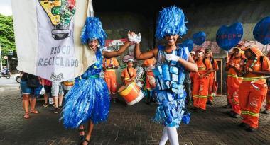 Mestre sala e porta bandeira do Bloco Reciclado com adereços azuis de material reciclado. Ao fundo, outros integrantes do bloxo, com instrumentos musicais e uniforme laranja da SLU.