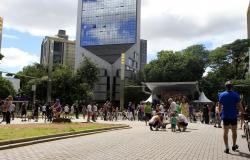 Mais de trinta pessoas passeiam no cruzamento das avenidas Getúlio Vargas com Cristóvão Colombo, durante o dia. Ao fundo, um palco e prédios se destacam.